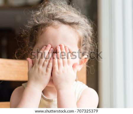 Shutterstock Close up of little girl with hands over eyes playing peekaboo (selective focus)
