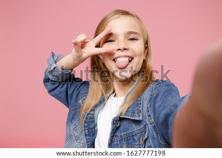 Close up of little kid girl 15 year old in denim jacket isolated on pastel pink wall background. Childhood lifestyle concept. Mock up copy space. Doing selfie pov on mobile phone showing victory sign Stock photo ©