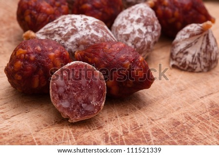 Close up of little salami sausages on a wooden board