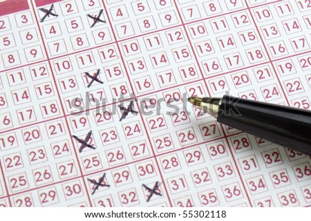 close up of lottery ticket and pen