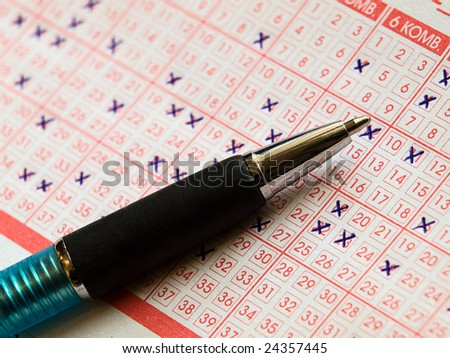 Close up of lottery ticket with a  marked numbers and a  pencil.