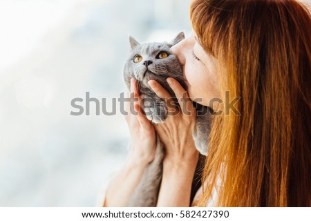 Close up of lovely middle-aged redhead woman kissing gray cat.  #582427390