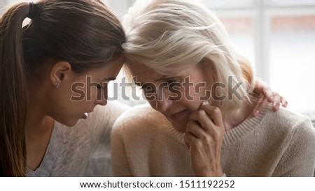 Close up of loving millennial adult daughter and elderly crying mom feel sad depressed share family loss grief together, supportive grownup female hug comfort unhappy senior mother show love and care