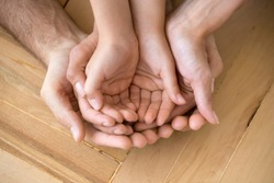 Close up of loving mom dad and kid hold hands on floor palms up together express closeness and unity, caring parents join stack arms with child show devotion, support and bonding. Family value concept