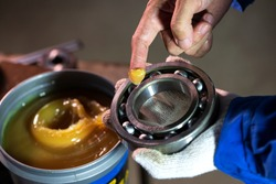 Close up of lubricant grease in hand Mechanic for putting into ball bearing in the industrial factory, Mechanic Industrial Concept