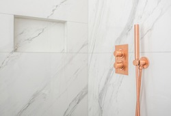 Close Up Of Luxurious White And Gray Marble Tile Shower With Copper Fixtures.