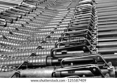 Close-up of M16 rifles stacked in series. B&W