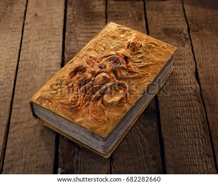 Stock Photo Close up of magic book with golden cover and marine monster image. Mystic still life with scary occult objects, horror Halloween and black magick concept