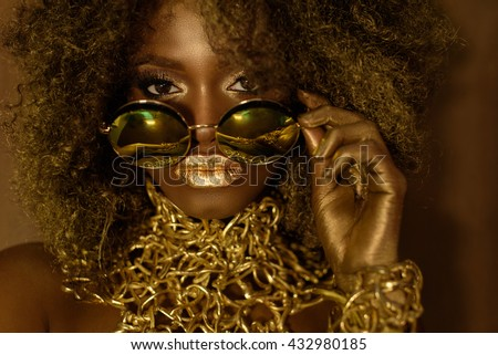 Close-up of magic golden african american female model in massive sunglasses with bright glitter makeup, glossy hairstyle and big red lips posing on the studio background