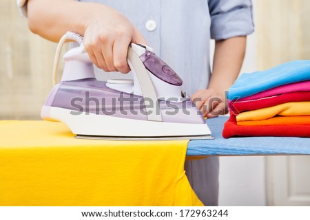 Close-up Of Maid Ironing Clothes On Ironing Board
