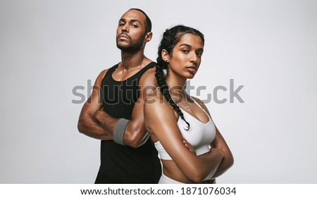 Close up of male and female athlete standing with arms crossed. Couple in fitness wear standing together at the gym. Foto stock ©