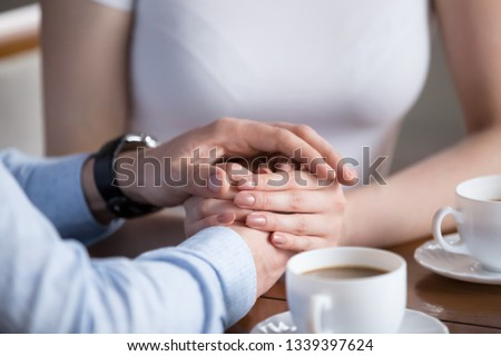 Close up of male and female hands. Millennial couple gently holding each other with hands. Young pair having romantic breakfast. Helping, taking care, trust in marriage, love and support concept #1339397624