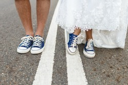 close up of male and female legs wearing sneakers on the road.