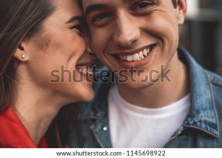 Close up of male and female smiling faces. Loving couple is standing with delight and embracing. Affectionate girl is kissing boyfriend and laughing #1145698922