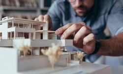Close up of male architect hands making model house. Man architect working in the office.
