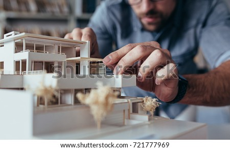 Close up of male architect hands making model house. Man architect working in the office. #721777969