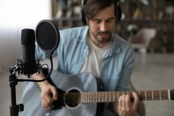 Close up of male artist or compose play on guitar sing record new song or single on microphone at home studio. Young man singer in headphones use musical instrument compose music. Hobby concept.