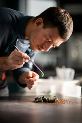 Close-up of male chef accurate holding tweezers in his hand with ingredient for preparing fusion cuisine dish