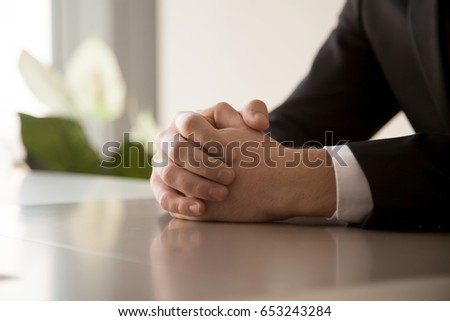 Close up of male clasped hands clenched together on table, businessman preparing for job interview, concentrating before important negotiations, thinking or making decision, business concept #653243284