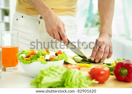Close-up of male cutting cucumber while cooking salad in the kitchen - stock photo