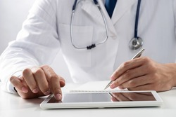 Close up of male doctor hands using tablet computer. Physician in white medical uniform with stethoscope sitting at desk. Modern technology in examination and diagnosis. Medical digital application
