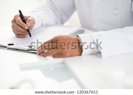 Close-up of male doctor hands with pen over medical document