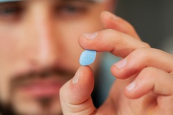 Close up of male doctor holding pill for men health