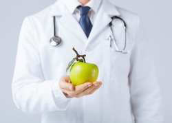 close up of male doctor with green apple