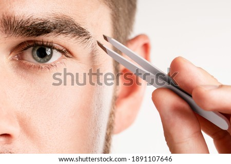 Close-up of male eye and tweezers for eyebrow grooming and shape correction ストックフォト ©