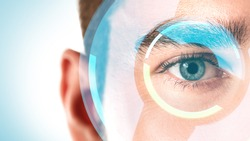 Close-up of male eye with HUD display. Concepts of augmented reality and biometric iris recognition or visual acuity check-up