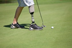 Close Up Of Male Golfer With Artificial Leg Putting Ball On Green