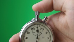 Close-up of male hand holding analogue stopwatch on green background. Time start with old chronometer man presses start button in the sport concept. Time management concept.