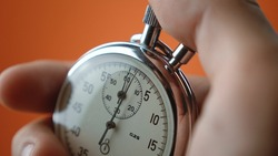 Close-up of male hand holding analogue stopwatch on orange background. Time start with old chronometer man presses start button in the sport concept. Time management concept.