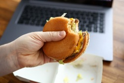 Close-up of male hand holding cheeseburger. Worker eating fast-food at workplace in office. Laptop and box on wooden table. Junk food and lunch break concept