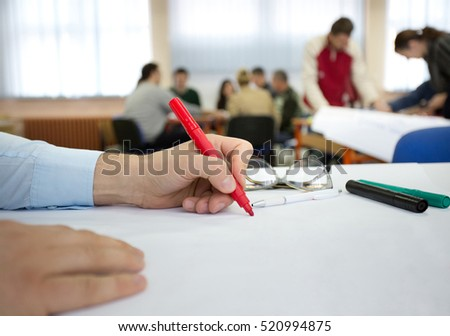 Close up of male hand in shirt writing notes on white chart during workshop #520994875