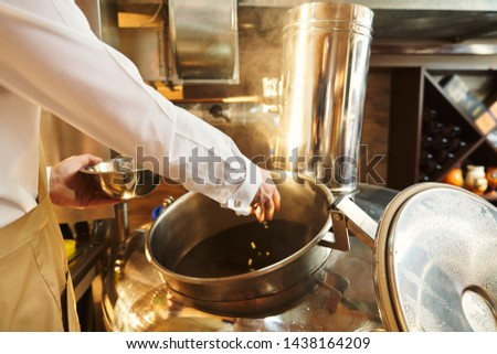 Close up of male hand of brewer adding hops in beer wort in metallic brew kettle. Modern technology of brewing beer. Stock photo ©