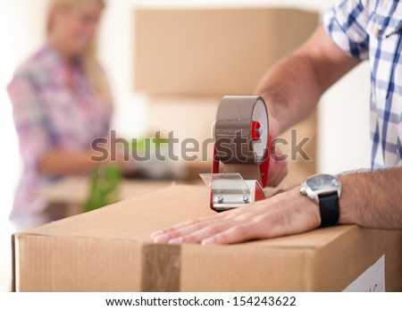 Close up of male hand packing cardboard box, concept moving house #154243622