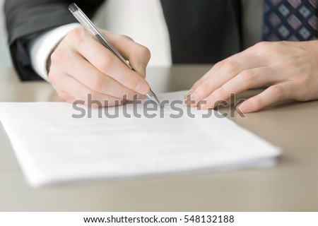 Close up of male hand putting signature in the contract, entering into the new contract, written statement declaring the price. Business partnership concept