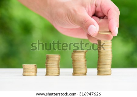 Close up of male hand stacking gold coins with green bokeh background ,Business Finance and Money concept
