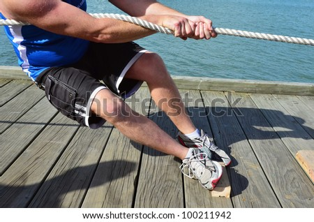 Close up of male hands and body pulling a rope in a tug of war game.
