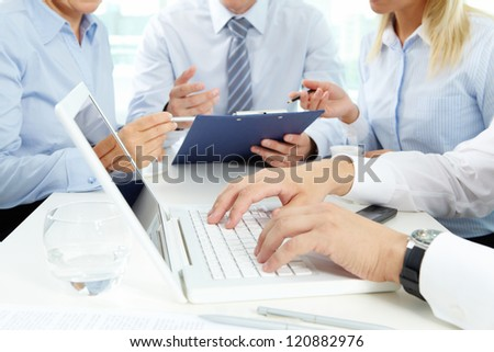 Close-up of male hands during work on the laptop, his colleagues holding a discussion in the background - stock photo