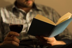 Close up of male hands holding book and glass of wine