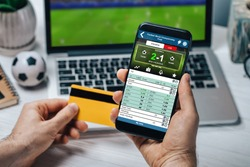 Close up of male hands holding credit card and mobile phone. Man collecting his prize sending money to card after winning it at bookmaker's website betting to his favourite team.