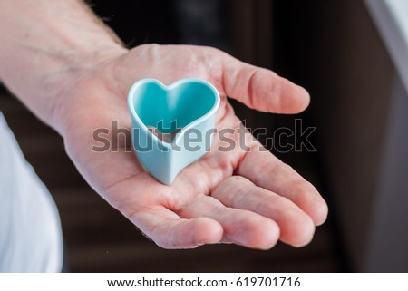 close up of male hands holding heart . offer of marriage. plastic baking mold heart form #619701716