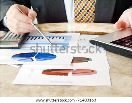Close-up of male hands holding pen over financial  charts