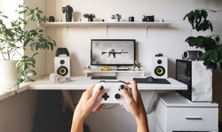 Close-up of male hands holding white wireless gamepad against white computer dream desk.