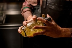 close-up of male hands of bartender in which he holds glassy shaker with bright cold cocktail