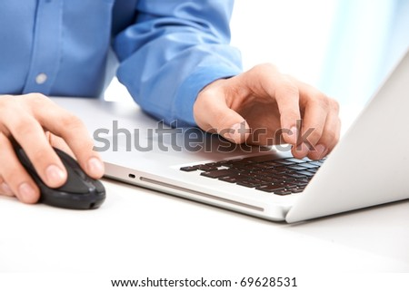 Close-up of male hands on mouse and over black keyboard of laptop during typing