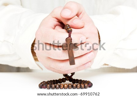 Close up of male hands praying with rosary