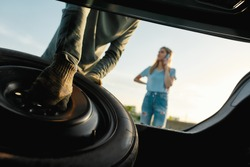 Close up of male hands taking out spare wheel, Man going to change car wheel while helping young woman with her broken auto, Low angle, Selective focus, Horizontal shot